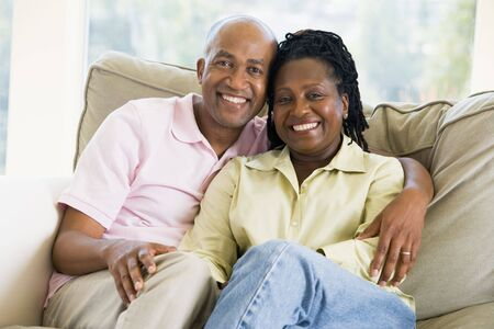 Couple relaxing in living room and smiling Stock Photo - 3472618