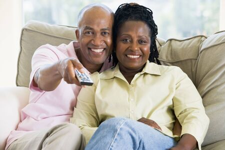 remote control: Couple relaxing in living room holding remote control and smiling