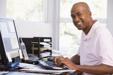 ordinateur bureau: L'homme dans la maison par ordinateur de bureau et souriant