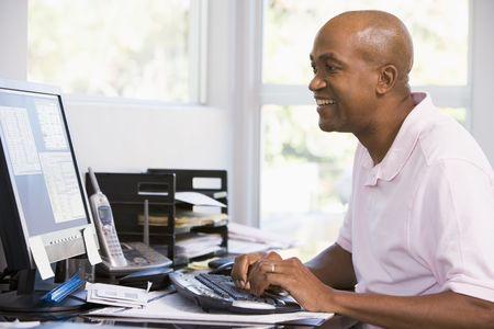 usando computadora: Hombre en oficina en casa usando la computadora y sonriente  Foto de archivo