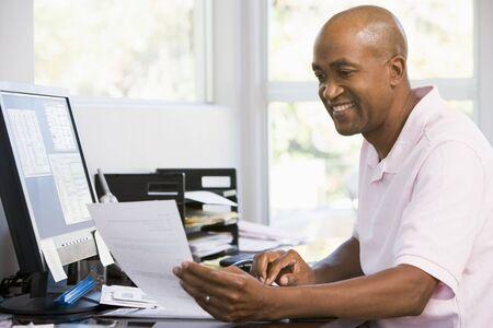 using the computer: Hombre en oficina en casa usando la computadora y sonriente  Foto de archivo
