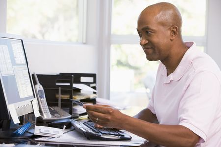 Man in home office using computer holding credit card and smiling Stock Photo - 3458876