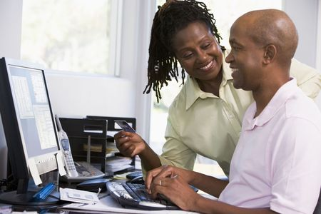 Couple in home office with credit card using computer and smiling photo