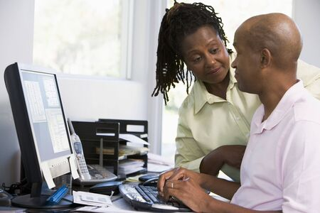 Couple in home office using computer photo