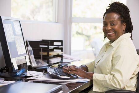 ordinateur bureau: Femme dans le bureau � domicile en utilisant l'ordinateur et le sourire