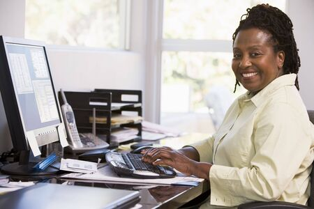 Woman in home office using computer and smiling Stock Photo - 3460741