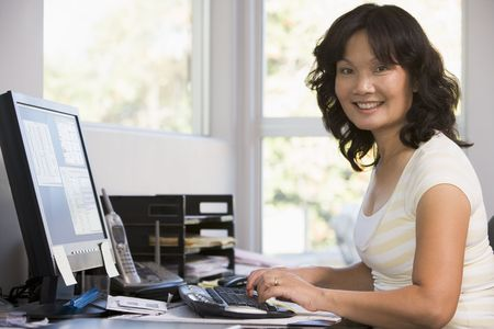 home office desk: Woman in home office using computer and smiling