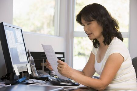 Woman in home office with computer and paperwork photo