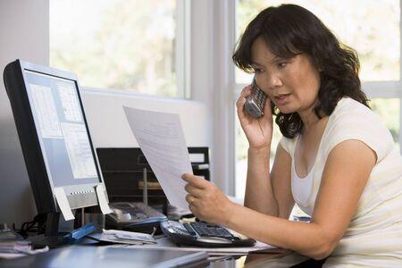 Donna in ufficio con documenti utilizzando telefono