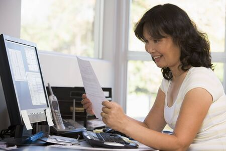 Woman in home office with computer and paperwork smiling photo