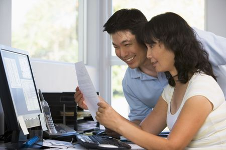 asian working woman: Couple in home office with computer and paperwork smiling