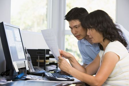 Couple in home office with computer and paperwork pointing photo