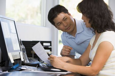 Couple in home office with computer and paperwork Stock Photo - 3460879