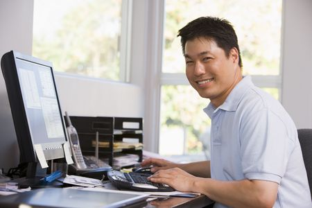 home office desk: Man in home office using computer and smiling Stock Photo