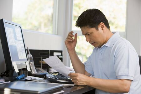Man in home office with computer and paperwork frustrated photo