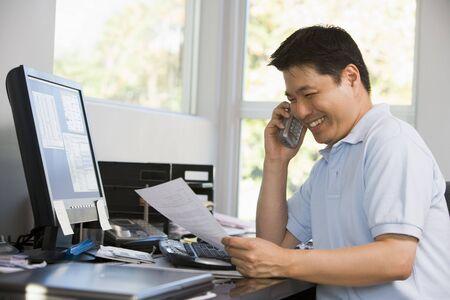 calling: El hombre en la oficina en casa con el ordenador y el papeleo en el tel�fono sonriendo Foto de archivo
