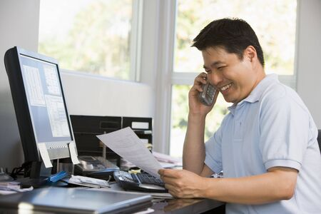 Man in home office with computer and paperwork on telephone smiling Stock Photo - 3460580