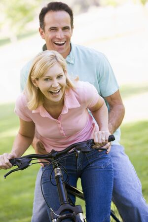 Couple on one bike outdoors smiling photo
