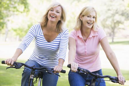 Two friends on bikes outdoors smiling photo