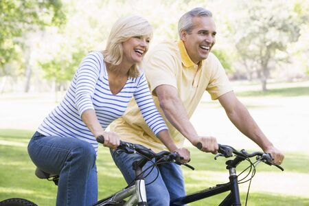 Couple on bikes outdoors smiling photo