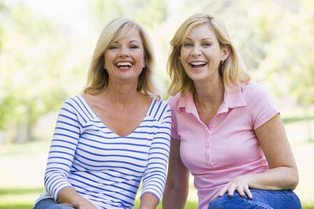 two friends: Two women sitting outdoors smiling