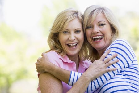 Two women outdoors hugging and smiling photo