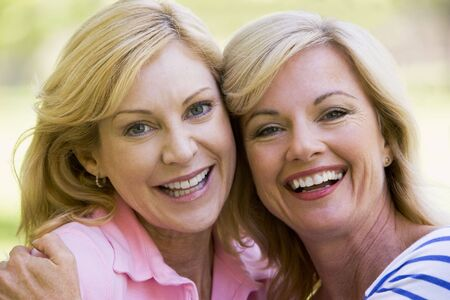 women sitting: Two women outdoors embracing and smiling