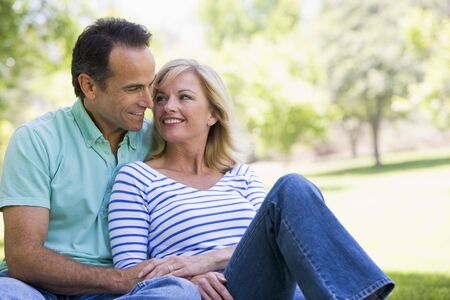 Couple relaxing outdoors in park smiling Stock Photo - 3471609