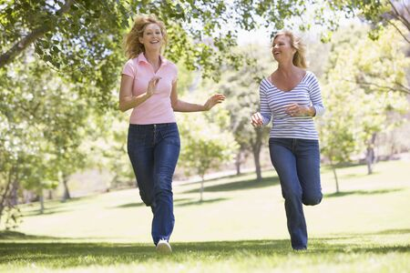 active life: Two women running in park and smiling Stock Photo
