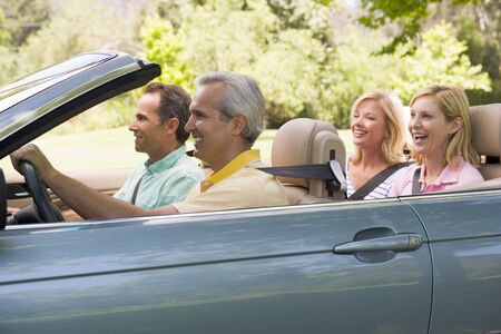 Two couples in convertible car smiling photo