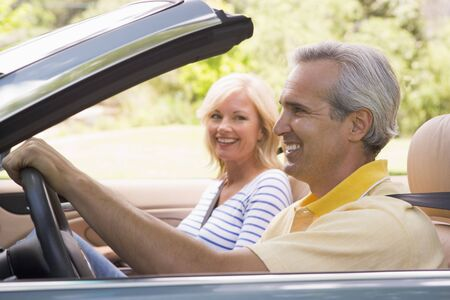 woman driving car: Couple in convertible car smiling Stock Photo