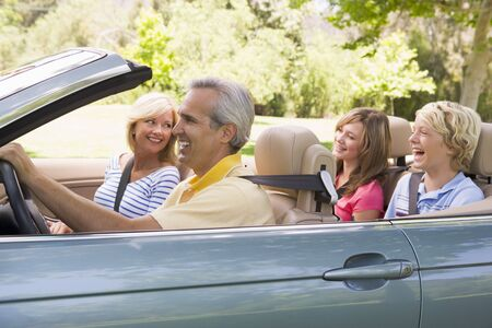 Family in convertible car smiling Stock Photo - 3471046