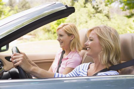 woman driving car: Two women in convertible car smiling