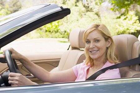 convertible car: Woman in convertible car smiling