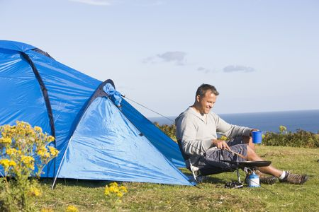 campsite: Man camping outdoors and cooking Stock Photo