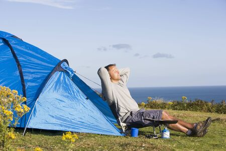 campground: Man camping outdoors and cooking Stock Photo