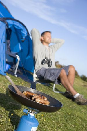 Man camping outdoors and cooking Stock Photo - 3458908