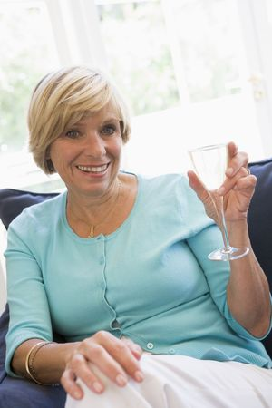 Woman sitting in living room with drink smiling