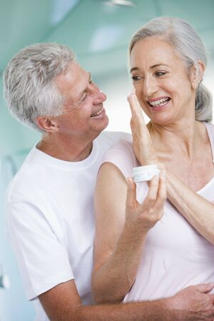 couple bathroom: Couple embracing at a spa holding cream and smiling