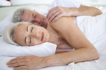 couple cuddling: Couple lying in bed together sleeping