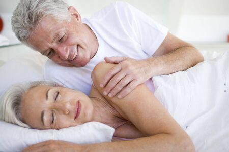 nightclothes: Man waking woman lying in bed sleeping Stock Photo