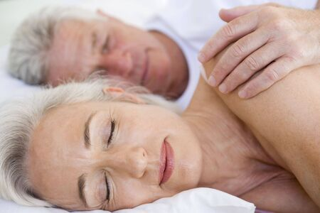 Couple lying in bed together sleeping photo