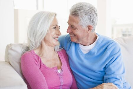 Couple relaxing in living room and smiling Stock Photo - 3475338