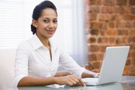 Businesswoman in office with laptop smiling photo