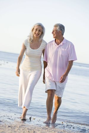 mature couple: Couple at the beach holding hands and smiling