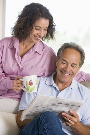 Couple relaxing with a newspaper smiling photo