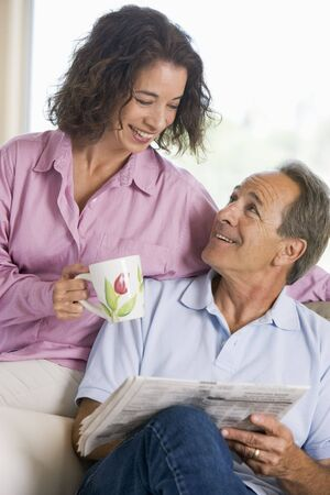 Couple relaxing with a newspaper smiling Stock Photo - 3475314