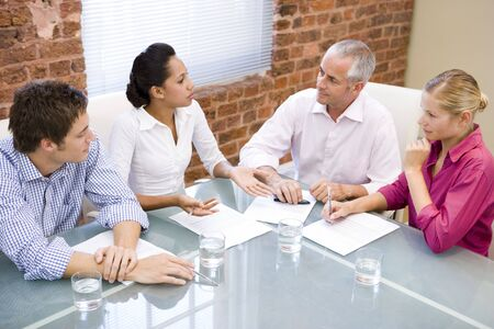 boardroom meeting: Four businesspeople in boardroom meeting Stock Photo