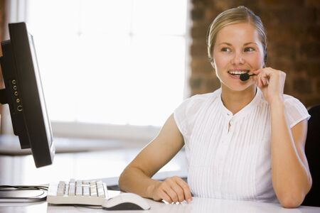 Businesswoman wearing headset in office smiling photo