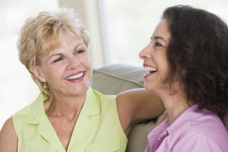 two people talking: Two women in living room talking and smiling